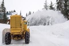 黄色雪犁清洁山路 免版税库存照片