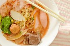 黄色面条用乌贼和鱼丸在红色汤中国语言叫雍Tau傅 免版税库存照片