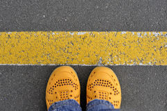黄色鞋子顶视图在柏油路的有黄线的 免版税库存图片
