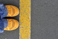 黄色鞋子顶视图在柏油路的有黄线的 免版税库存照片