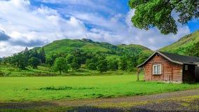 绿色领域和山与都市房子在英国 库存照片