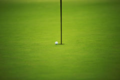 绿色领域和高尔夫球在孔 免版税库存图片