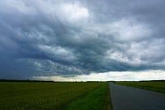 绿色领域和黑暗的云彩 免版税库存照片