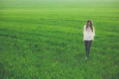 绿色领域的哀伤的孤独的女孩 免版税库存照片