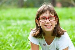 绿色领域的逗人喜爱的有残障的女孩。 库存图片