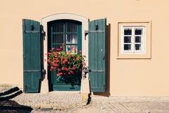 黄色颜色墙壁和葡萄酒称呼绿色门和开花的花 库存图片
