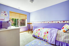 紫色颜色的明亮的快乐的卧室与五颜六色的卧具 库存图片