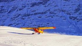 黄色飞机着陆在瑞士冬天山滑雪reso的 库存照片