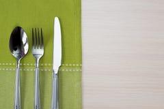 绿色餐巾刀子叉子和匙子 免版税库存照片
