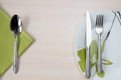绿色餐巾刀子叉子板材 免版税库存图片