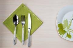 绿色餐巾刀子叉子板材 免版税库存照片
