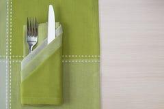 绿色餐巾刀子和叉子 免版税库存图片