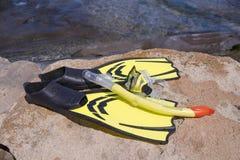 黄色鸭脚板和潜水面具在海滩 免版税库存照片