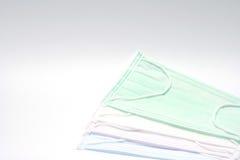 绿色,桃红色,浅兰和白色耳朵圈一次性面罩重叠,使用为盖嘴和鼻子 它防止受到 库存照片