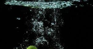 黄色, Citrus Limonum, aurantifolia的柑橘,结果实落入水反对黑背景, 股票录像