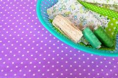 绿色织品、鞋带和螺纹在一个绿色篮子在紫色背景 免版税库存图片