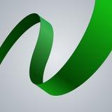 绿色织品在灰色背景的弯曲的丝带 免版税图库摄影