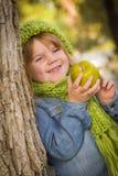 戴绿色围巾和帽子的女孩吃苹果计算机外面 免版税库存照片