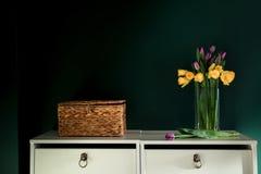 黄色黄水仙开花与开花在有绿色墙壁下个邪恶的篮子的花瓶的紫色郁金香 库存图片