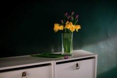 黄色黄水仙开花与开花在有绿色墙壁下个邪恶的篮子的花瓶的紫色郁金香 库存照片
