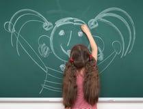 画绿色黑板背景的,暑期学校假期概念的红色镶边礼服的女小学生孩子愉快的人 免版税库存图片