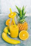 黄色结果实在瓶的圆滑的人有吸管和新鲜的成份的:香蕉、桔子和菠萝,正面图 免版税库存照片