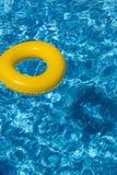 黄色水池浮游物,在凉快的蓝色refreshi的水池圆环 图库摄影
