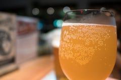 黄色玻璃使与泡影的工艺啤酒变冷 图库摄影