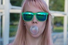 绿色玻璃的女孩与长的头发喘气chewi泡影  免版税库存照片