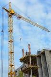 黄色建筑用起重机和未完成的大厦与金属具体结构在蓝天背景与白色 免版税库存照片
