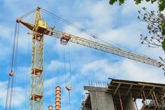 黄色建筑用起重机,修造的金属具体结构,树的绿色分支 海岸线绿色水平的图象照片撒丁岛海运天空植被 免版税图库摄影