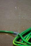 绿色水管漏的喷洒的水 库存照片