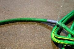 绿色水管漏的喷洒的水 免版税库存照片
