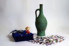 绿色水罐酒和一个蓝色礼物盒 免版税库存图片