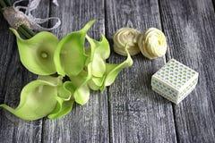 绿色黄色水芋百合花束与纸板箱和蛋白软糖的在灰色木背景 库存图片