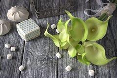 绿色黄色水芋百合花束与纸板箱和蛋白软糖的在灰色木背景 库存照片