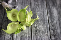 绿色黄色水芋百合花束在灰色木背景的 库存照片