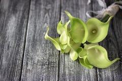 绿色黄色水芋百合花束在灰色木背景的 免版税库存照片