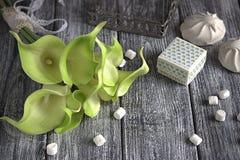 绿色黄色水芋百合花束用蛋白软糖和纸板箱在灰色木背景 库存图片