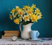 黄色黄水仙花束在一本白色水罐、闹钟和书的 库存图片