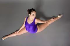 紫色紧身连衣裤的年轻女性柔术表演者在黑暗的背景 图库摄影