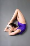 紫色紧身连衣裤的年轻女性柔术表演者在黑暗的背景 免版税库存图片