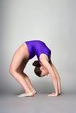 紫色紧身连衣裤的年轻女性柔术表演者在黑暗的背景 免版税库存照片