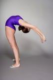 紫色紧身连衣裤的年轻女性柔术表演者在黑暗的背景 库存图片
