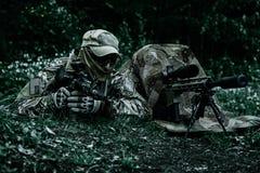 绿色贝雷帽的狙击手和监视人 免版税库存图片