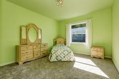 绿色kid& x27; 有木被雕刻的家具和灰色地毯的s卧室 库存图片