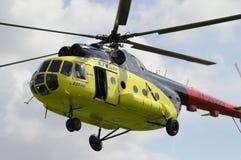 黄色MI-8直升机飞行反对与一开放doo的云彩 库存图片
