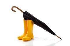 黄色rainboots和黑伞在白色 免版税库存照片