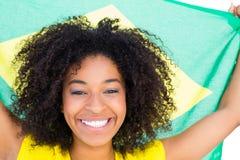 黄色T恤杉的俏丽的女孩拿着巴西旗子微笑对照相机的 免版税库存照片