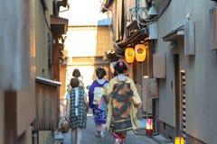 艺妓和maiko穿传统礼服和服走在街道上的一个小组 免版税库存照片